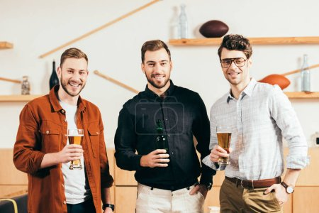 portrait of smiling men with beer in hands looking at camera in cafe