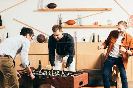 Foto de Hombre excitado mirando amigos jóvenes jugando fútbol de mesa en la cafetería - Imagen libre de derechos