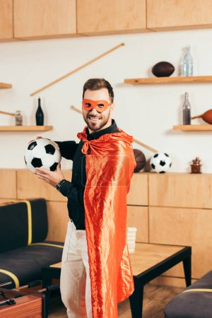 young smiling man in red superhero costume with soccer ball in cafe