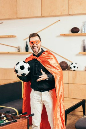 excited young man in red superhero costume with soccer ball in cafe