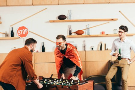 Foto de Joven alegres amigos jugando fútbol de mesa juntos en café - Imagen libre de derechos