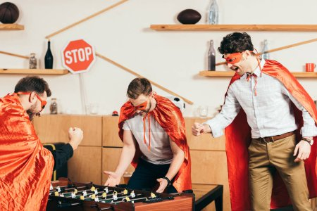 young friends in superhero costumes playing table soccer in cafe