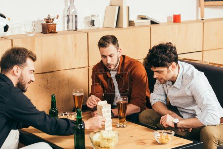 focused friends playing blocks wood game at tabletop with snacks and beer  in cafe