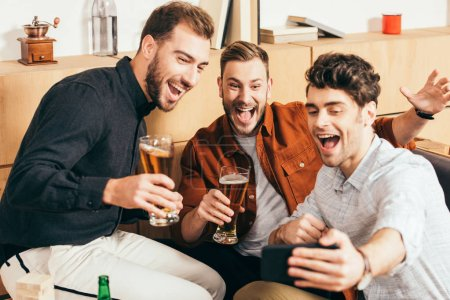 Foto de Amigos felizes con cerveza tomando selfie en smartphone en café - Imagen libre de derechos