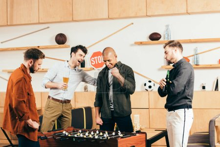 Photo for Multiracial young friends playing table football together in cafe - Royalty Free Image