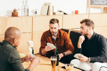 Photo pour Hommes multiculturels jouer aux cartes tout en passant du temps ensemble dans un café - image libre de droit