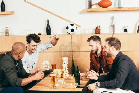 multicultural men playing cards while spending time together in cafe
