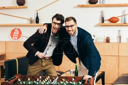 portrait of smiling businessmen with beer standing at table soccer in cafe