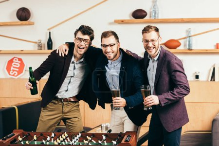 portrait of happy businessmen with beer standing at table soccer in cafe