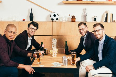 young multicultural businessmen with beer looking at camera spending time in cafe