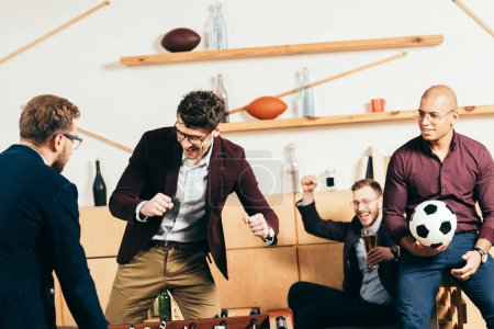multiracial businessmen playing table football while resting in cafe