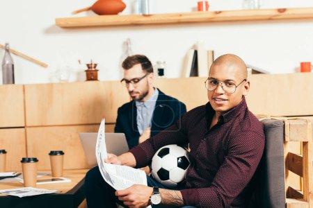 Photo pour Homme d'affaires afro-américain avec journal et collègue caucasien à proximité dans un café - image libre de droit
