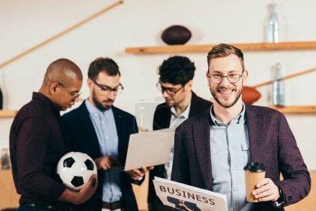 Photo pour Mise au point sélective d'homme d'affaires souriant avec café pour aller, Journal et multiethniques collègues utilisant portable derrière au café - image libre de droit