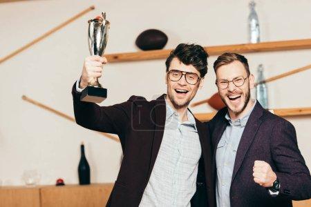 Photo pour Portrait d'hommes d'affaires heureux avec des champions gobelet dans le café - image libre de droit