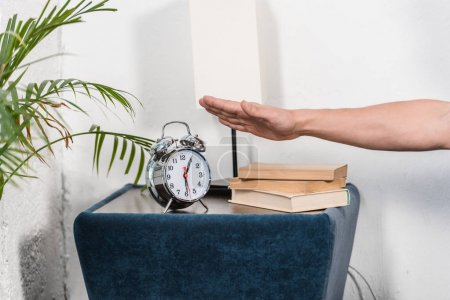 cropped image of man turning off alarm clock in morning at home