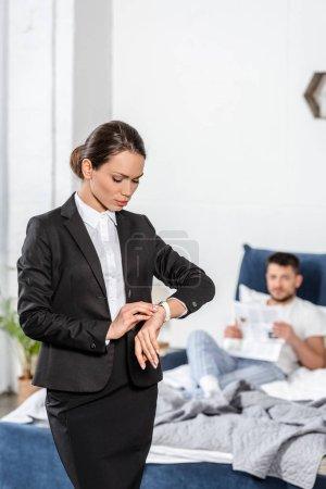 Photo pour Jolie petite amie en costume vérifier l'heure à la montre-bracelet et petit ami en pyjama lecture journal dans la chambre le matin, concept d'égalité des sexes - image libre de droit
