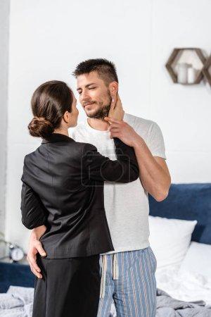 Photo pour Petite amie en costume étreignant petit ami en pyjama dans la chambre le matin en semaine, concept d'égalité des sexes - image libre de droit