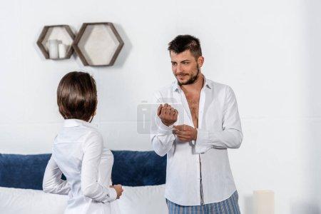 beau petit ami boutonnage brassard et regardant copine boutonner sa chemise au matin de la semaine dans le concept de chambre, féministe
