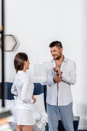 Photo pour Joyeux copain beau boutonnage brassard et regardant copine boutonner sa chemise au matin de la semaine dans la chambre, le concept de l'égalité entre les sexes - image libre de droit
