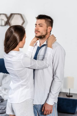 girlfriend fixing boyfriend shirt in morning in bedroom, social role concept
