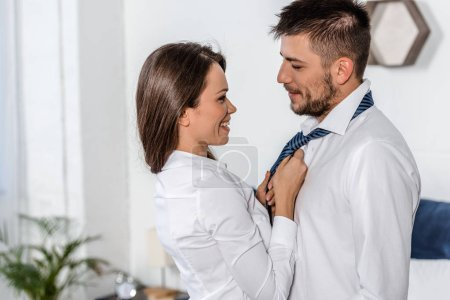 side view of smiling girlfriend tying boyfriend tie in morning on weekday in bedroom, social role concept