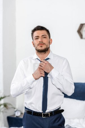 handsome man tying tie in morning in bedroom and looking at camera