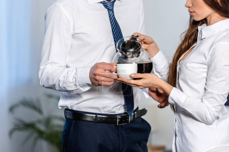 cropped image of girlfriend pouring coffee into boyfriend cup in morning at home, social role concept