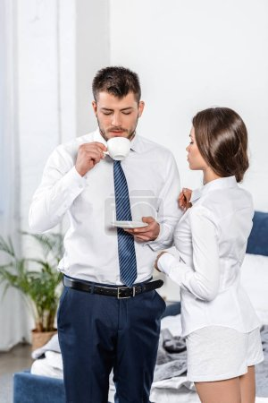 girlfriend waiting while boyfriend drinking coffee in morning at home, social role concept