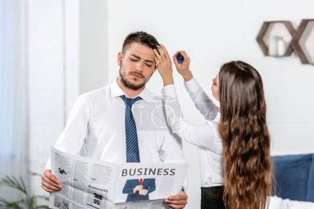 girlfriend styling boyfriend hair and he reading business newspaper at home, social role concept