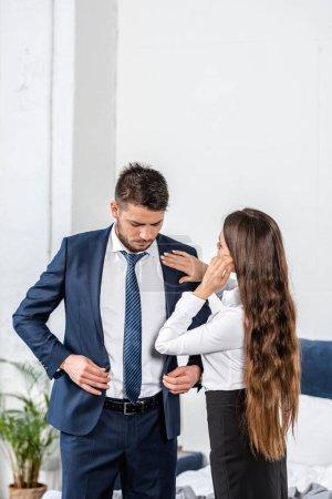 girlfriend fixing boyfriend jacket before work, social role concept