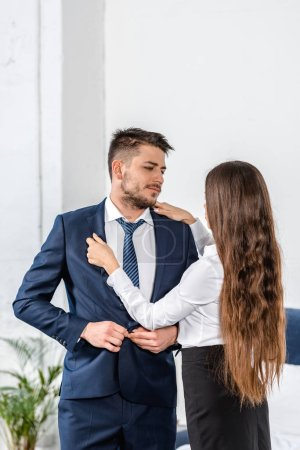 girlfriend fixing boyfriend jacket before work, gender stereotypes concept