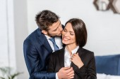 handsome boyfriend kissing smiling attractive girlfriend before work at home