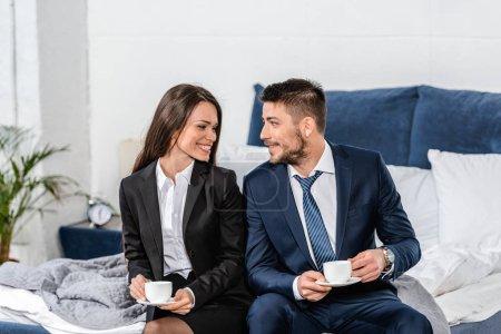 Photo pour Petite amie souriante et petit ami en costumes assis sur le lit et tenant des tasses de café le matin à la maison, concept d'égalité des sexes - image libre de droit