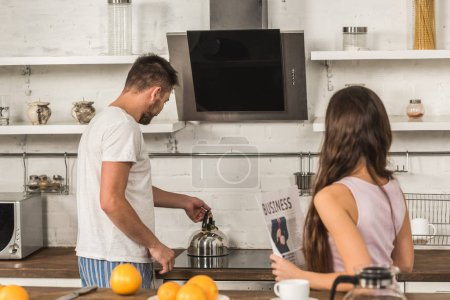 girlfriend holding business newspaper and boyfriend putting kettle on stove at home