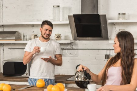 smiling girlfriend and boyfriend drinking coffee and looking at each other in morning at kitchen