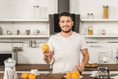 handsome smiling man holding orange and looking at camera in morning at kitchen