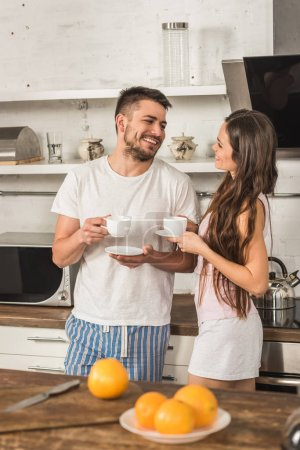 Photo for Smiling girlfriend and boyfriend holding cups of coffee and looking at each other in morning at kitchen - Royalty Free Image