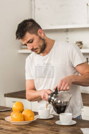 Photo for Handsome man pouring coffee into cup in morning at kitchen - Royalty Free Image