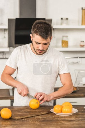Photo for Handsome man cutting oranges in morning at kitchen - Royalty Free Image