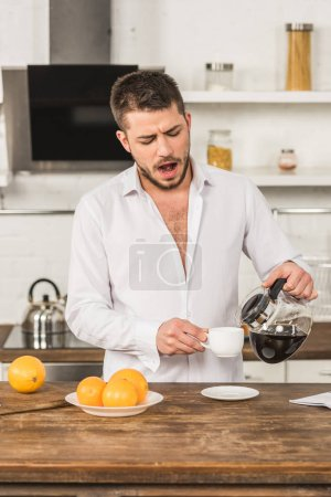 handsome man yawning and pouring coffee into cup in morning at kitchen