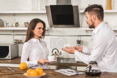 cheerful boyfriend and girlfriend in shirts standing with cups of coffee in morning at kitchen, gender equality concept