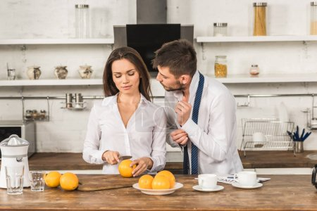 boyfriend buttoning cuff and girlfriend cutting oranges in kitchen, social roles concept