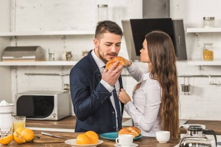 boyfriend eating croissant and girlfriend fixing his jacket in kitchen, sexism concept
