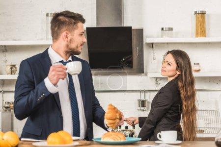 Photo pour Petit ami avoir le petit déjeuner et petite amie mettre la bouilloire sur cuisinière à domicile, notion de sexisme - image libre de droit