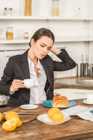 attractive woman in suit holding cup of coffee and touching hair in morning at kitchen