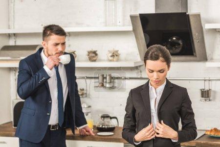 Photo pour Petit ami boire du café et en regardant de copine dans la matinée à la cuisine, le concept de l'égalité entre les sexes - image libre de droit