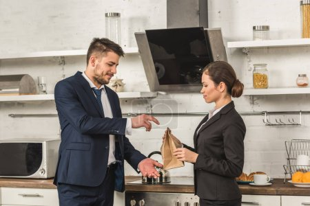 girlfriend giving lunch to boyfriend in morning at kitchen, social roles concept