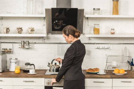 Photo for Attractive woman in suit putting kettle on stove in morning at kitchen - Royalty Free Image