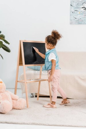 adorable african american child standing and writing on chalkboard