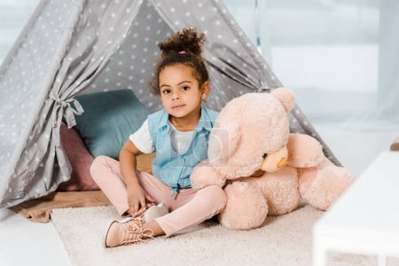 adorable african american child sitting on carpet with pink teddy bear and smiling at camera